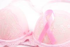 Bröstcancermedvetenhet, rosa band och rosa färgbehå på vita Backg Arkivfoto