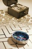 Bröstkorg av mynt med kompasset royaltyfri foto