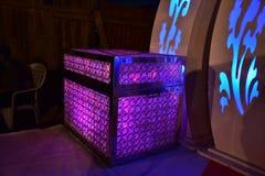 Bröstkorg av purpurfärgade ljus på etappen för ett bröllop Arkivbild