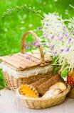 Brötchen in einem Weidenkorb und in einem Blumenstrauß von Feldblumen Stockbild