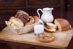 Brötchen mit Rosinen, Bagel und Brot und ein Glas Milch Lizenzfreies Stockfoto