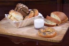 Brötchen mit Rosinen, Bagel und Brot und ein Glas Milch Stockbilder