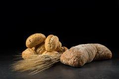 Brötchen und ciabatta, Brot auf dunklem Holztisch Gerste und frische Mischbrote lokalisiert auf schwarzem Hintergrund Lizenzfreie Stockfotos