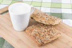 Brötchen und Milch auf hölzernem Brett, Frühstück Stockfotografie