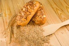 Brötchen und Ohren des Weizens auf dem Tisch Stockbild