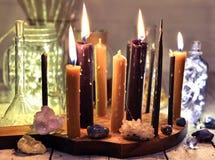 Brûlant bougies noires et de cru, cristaux et pierres minérales avec les bouteilles brillantes sur la table photos libres de droits