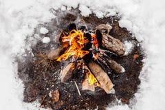 Brûlures de feu de camp dans la neige dans les bois feu de camp brûlant en hiver froid Neige, forêt et feu L'hiver tourisme photo libre de droits