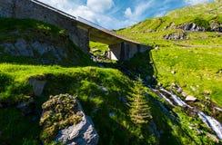 Brücke über dem Bach in den Bergen Stockbilder
