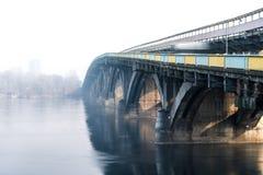 Brücke über dem Fluss am sonnigen Tag des Nebels Stockbild