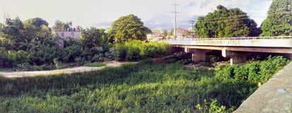 Brücke über dem Strom verseucht mit Abfall Lizenzfreie Stockfotos
