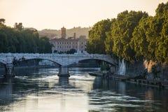 Brücke über dem Tiber-Fluss in Rom bei Sonnenuntergang mit Bäumen und Wasser lizenzfreie stockfotos