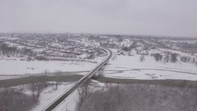 Brücke über einem gefrorenen Fluss im Winter in einer Kleinstadt stock video
