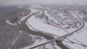 Brücke über einem gefrorenen Fluss im Winter in einer Kleinstadt nahe dem Wald stock video footage