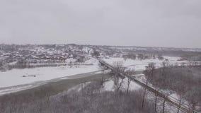 Brücke über einem gefrorenen Fluss im Winter, Luftbildfotografie stock footage