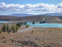 Brücke über einem Türkisblaufluß im argentinischen Patagonia Lizenzfreie Stockfotos