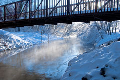 Brücke über einfrierendem Nebenfluss Lizenzfreie Stockfotos