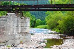 Brücke über felsigem Gebirgsfluss Lizenzfreies Stockfoto