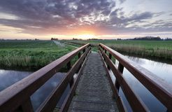Brücke über Fluss bei schönem Sonnenaufgang lizenzfreie stockbilder