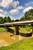 Brücke über Muddy Stream und blauem bewölktem Himmel Stockfotografie