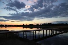 Brücke über ruhig Wasser im Sonnenuntergang lizenzfreies stockbild