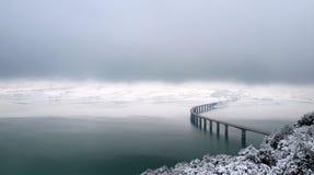 Brücke über winterlichem See Lizenzfreies Stockbild