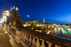 Brücke Alexander-III nachts und Seine mit Boot Stockbilder