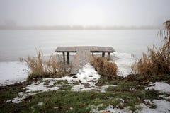 Brücke auf dem Ufer von einem Wintersee stockfotos