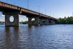 Brücke auf einem Fluss gegen einen blauen Himmel und Wolken Lizenzfreie Stockfotografie