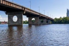Brücke auf einem Fluss gegen einen blauen Himmel und Wolken Lizenzfreies Stockfoto