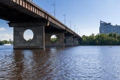 Brücke auf einem Fluss gegen einen blauen Himmel und Wolken Lizenzfreies Stockbild