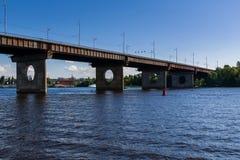 Brücke auf einem Fluss gegen einen blauen Himmel und Wolken Stockbilder