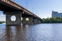 Brücke auf einem Fluss gegen einen blauen Himmel und Wolken Lizenzfreie Stockbilder