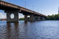 Brücke auf einem Fluss gegen einen blauen Himmel und Wolken Stockfotografie