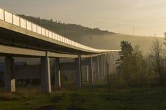 Brücke in den Bergen während des Sonnenaufgangs Lizenzfreies Stockfoto