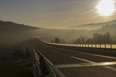 Brücke in den Bergen während des Sonnenaufgangs Stockbilder
