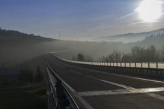 Brücke in den Bergen während des Sonnenaufgangs Lizenzfreie Stockfotografie