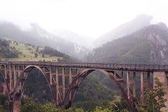 Brücke in den nebeligen Bergen Stockfotos