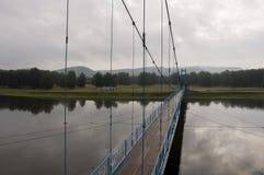 Brücke der blauen Farbe über dem Fluss und seiner Reflexion Grauer Himmel und graues Wasser Grüner Wald und montains weit weg Lizenzfreies Stockfoto