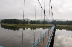 Brücke der blauen Farbe über dem Fluss und seiner Reflexion Grauer Himmel und graues Wasser Grüner Wald und montains weit weg Stockfotos