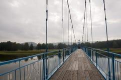 Brücke der blauen Farbe über dem Fluss und seiner Reflexion Grauer Himmel und graues Wasser Grüner Wald und montains weit weg Lizenzfreie Stockbilder