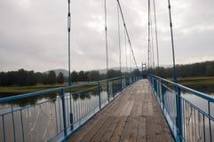 Brücke der blauen Farbe über dem Fluss und seiner Reflexion Grauer Himmel und graues Wasser Grüner Wald und montains weit weg Lizenzfreies Stockbild
