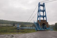 Brücke der blauen Farbe über dem Fluss und seiner Reflexion Grauer Himmel und graues Wasser Grüner Wald und montains weit weg Stockfotografie