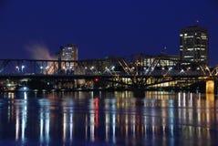 Brücke, die über einen ruhigen Fluss nachdenkt Stockfotografie