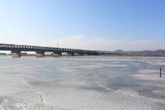 Brücke durch Fluss deckte Eis ab Stockfotos