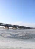 Brücke durch Fluss deckte Eis ab Lizenzfreies Stockfoto