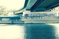 Brücke in Fluss mit Graffiti Stockbild