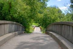 Brücke im sonnigen Bach-Park Stockfotografie