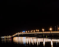 Brücke mit den Lichtern, die im Wasser sich reflektieren Stockbild