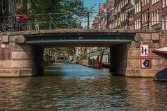 Brücke mit Eisenbalustrade und -fahrräder, alte Backsteinbauten und sonniger blauer Himmel in Amsterdam Lizenzfreies Stockbild