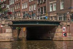Brücke mit Eisenbalustrade und -fahrräder, alte Backsteinbauten und sonniger blauer Himmel in Amsterdam Stockfotografie